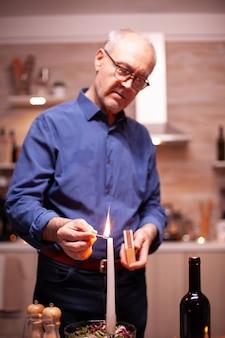 Älterer mann, der eine kerze mit streichhölzern in der küche für ein romantisches abendessen mit seiner frau anzündet. älterer alter ehemann, der festliches essen mit gesundem essen für die jubiläumsfeier zubereitet und am tisch sitzt.