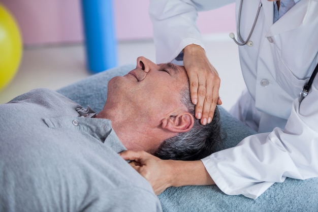 Älterer mann, der eine nackenmassage vom physiotherapeuten erhält