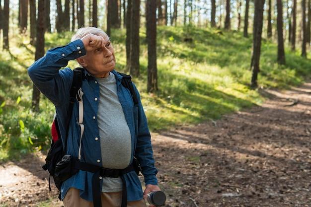 Älterer mann, der eine pause vom reisen im freien mit rucksack macht