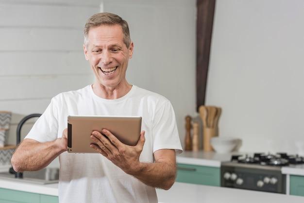 Älterer mann, der eine tablette hält