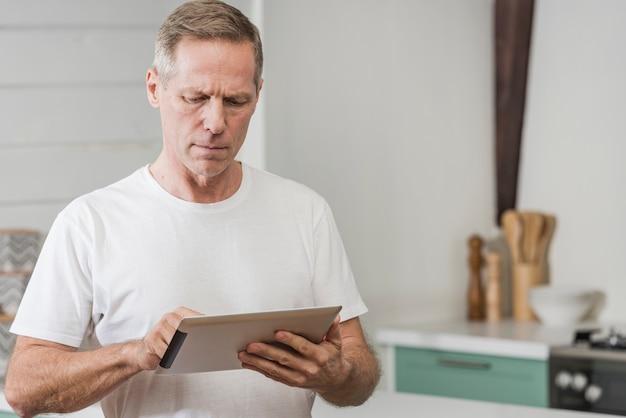 Älterer mann, der eine tablette mit kopienraum hält