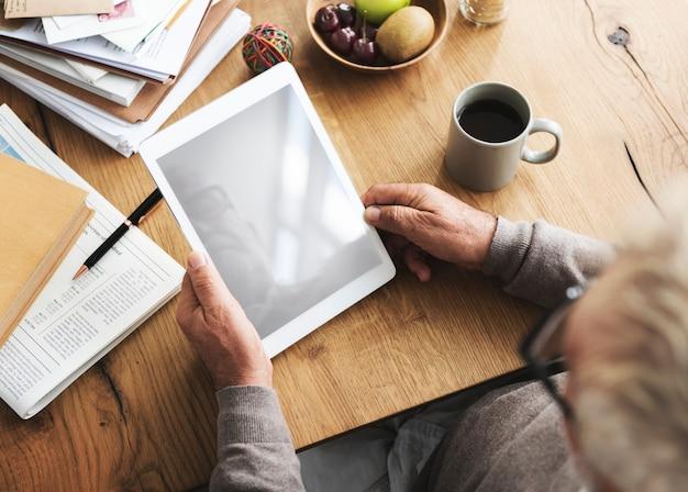 Älterer mann, der eine tablette verwendet