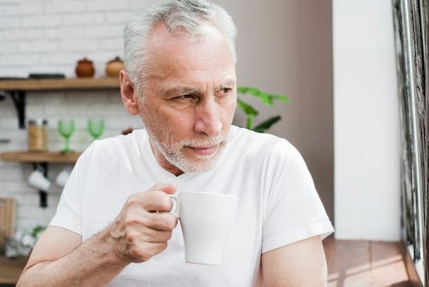 Älterer mann, der einen kaffee trinkt