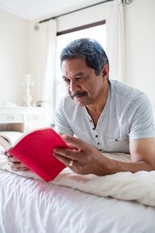 Älterer mann, der einen roman im wohnzimmer liest