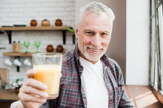 Älterer mann, der einen saft isst