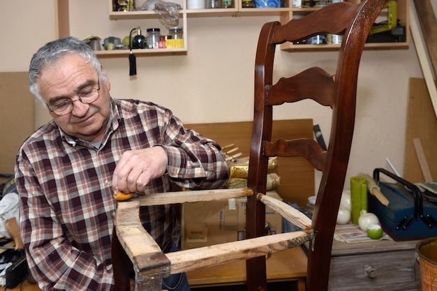 Älterer mann, der einen stuhl wieder herstellt