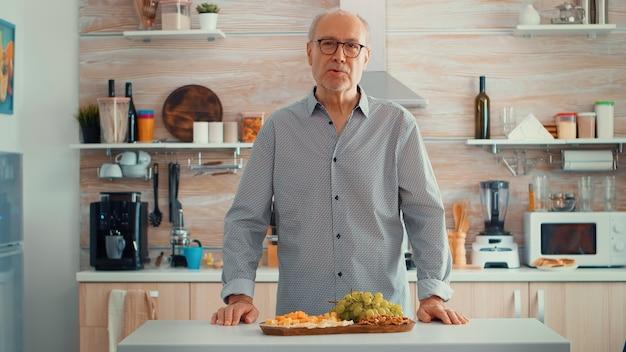 Älterer mann, der einen videoanruf in der küche hat, während seine familie das abendessen im hintergrund zubereitet. pov online-internet-moderne konferenz, chatten, kommunikation, chat-gesprächsanruf über webcam