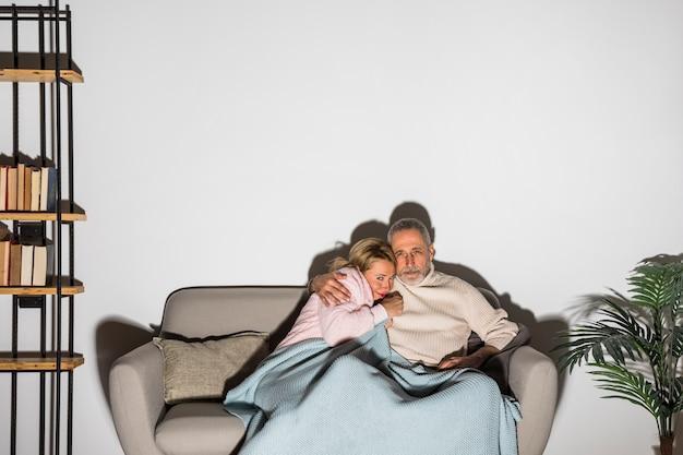 Älterer mann, der erschrockene frau umarmt und auf sofa fernsieht