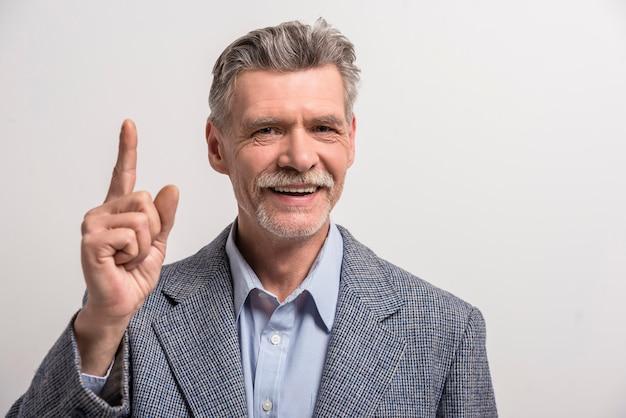 Älterer mann, der etwas durch seinen zeigefinger zeigt.