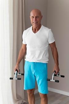 Älterer mann, der fitnesszubehör drinnen verwendet