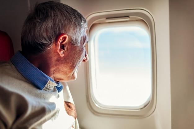 Älterer mann, der flugzeugfenster betrachtet.