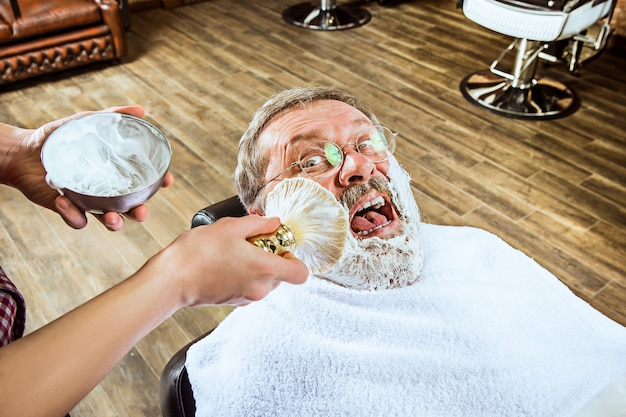 Älterer mann, der friseur im friseurladen besucht