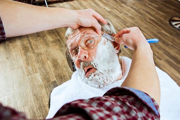 Älterer mann, der friseur im friseurladen besucht.