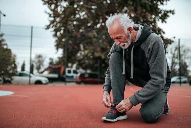 Älterer mann, der für einen lauf auf stadion im freien sich vorbereitet.