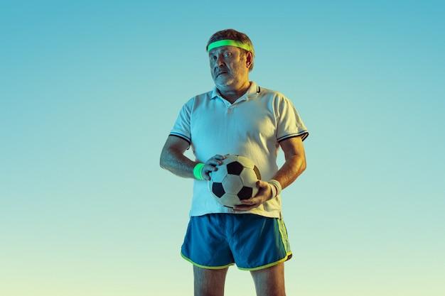 Älterer mann, der fußball in sportbekleidung auf gradientenhintergrund und neonlicht spielt