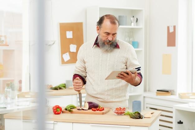 Älterer mann, der gemüse in der küche kocht