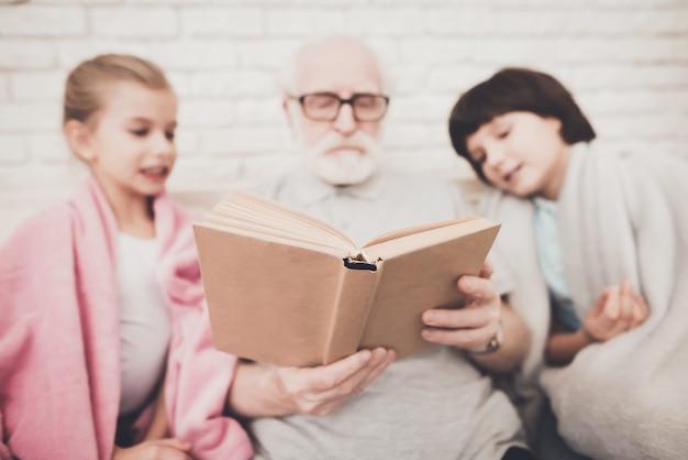Älterer mann, der geschichtenbuch für zwei enkelkinder liest