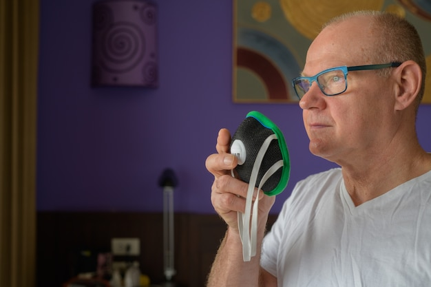 Älterer mann, der gesichtsmaske hält, um vor verschmutzungssmog zu schützen