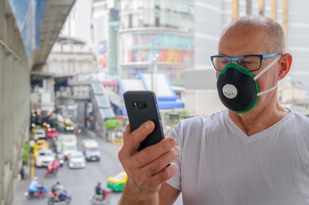Älterer mann, der gesichtsmaske verwendet, um vor verschmutzungssmog in der stadt zu schützen
