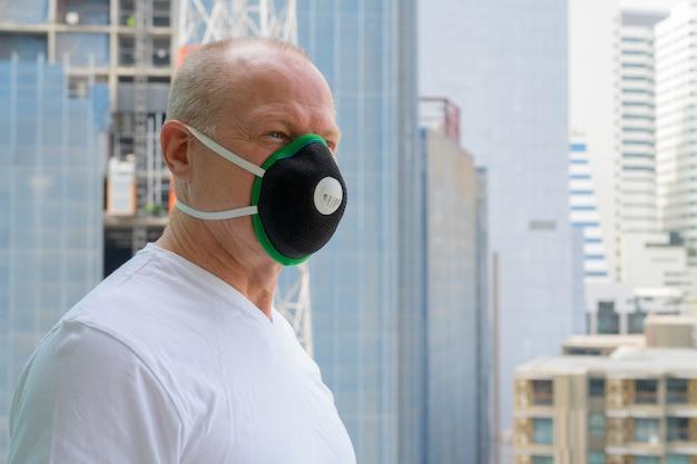 Älterer mann, der gesichtsmaske verwendet, um vor verschmutzungssmog zu schützen