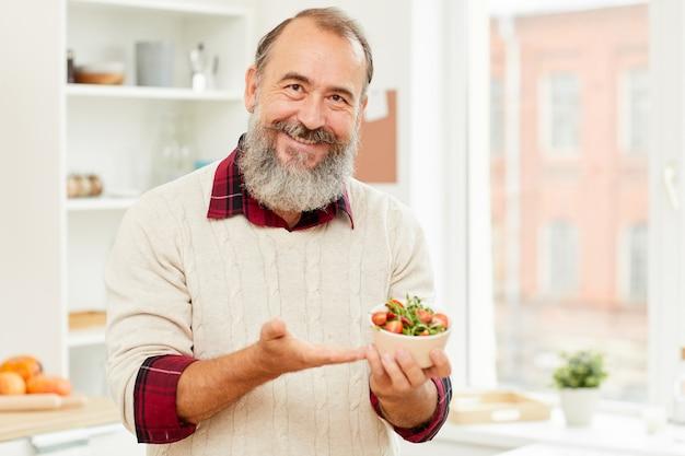 Älterer mann, der gesunden salat hält