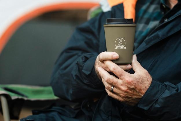 Älterer mann, der grüne wiederverwendbare tasse hält