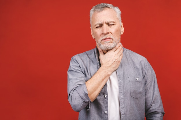 Älterer mann, der halsschmerzen hat und seinen hals berührt und eine isolierte freizeitkleidung trägt. schwer zu schlucken.