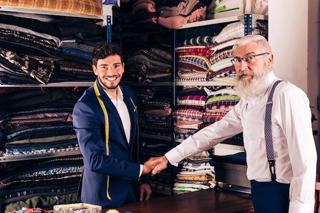 Älterer mann, der hand mit lächelndem jungem männlichem schneider in seinem shop rüttelt
