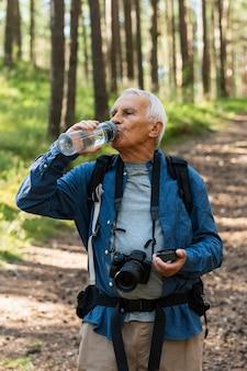 Älterer mann, der hydratisiert bleibt, während er die natur erkundet