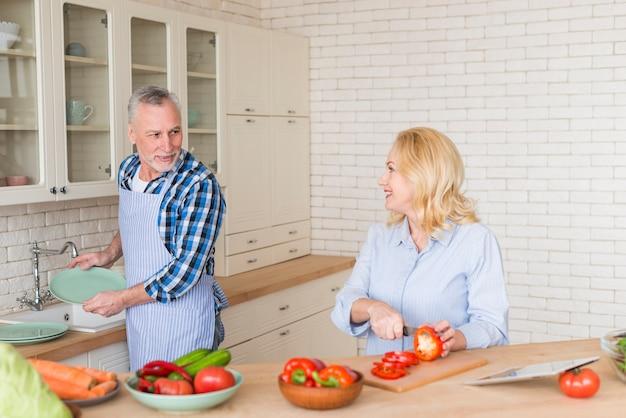 Älterer mann, der ihrer frau hilft, grünen pfeffer mit messer in der küche zu schneiden