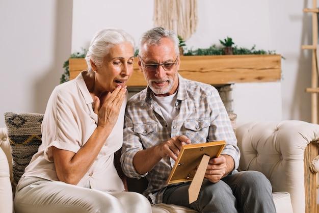 Älterer mann, der ihrer überraschten frau fotorahmen zeigt, die auf sofa sitzt