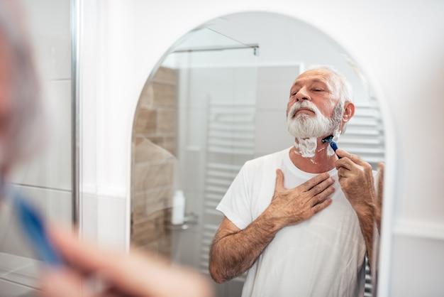 Älterer mann, der im badezimmer, reflexion im spiegelbild sich rasiert.