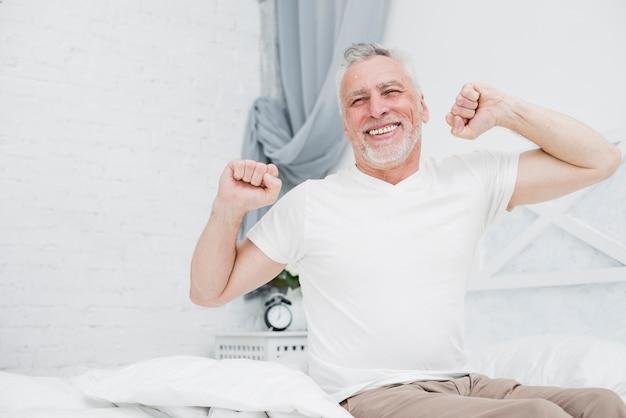 Älterer mann, der im bett aufwacht