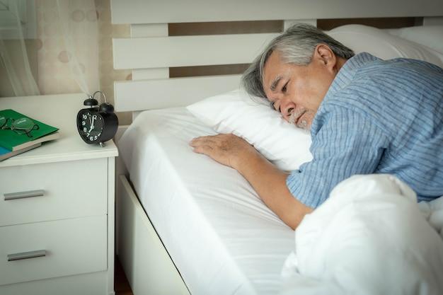 Älterer mann, der im bett leidet, kann nicht an schlaflosigkeit schlafen, älterer mann, alter mann möchte morgens nicht aus dem bett aufwachen - konzept für ältere schlaflosigkeit