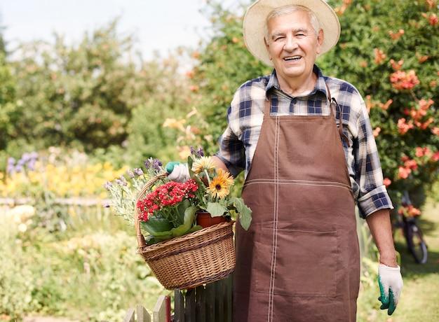 Älterer mann, der im feld mit blumen arbeitet