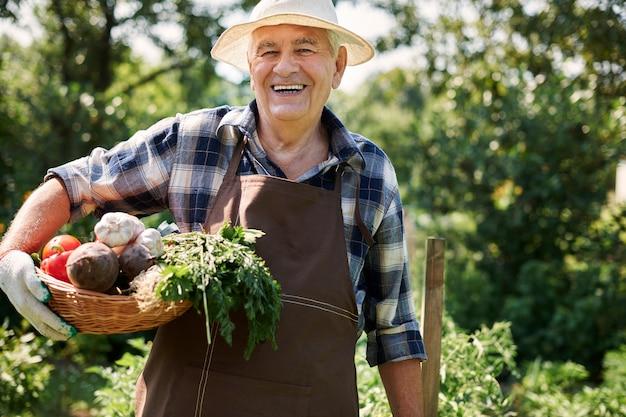 Älterer mann, der im feld mit gemüse arbeitet