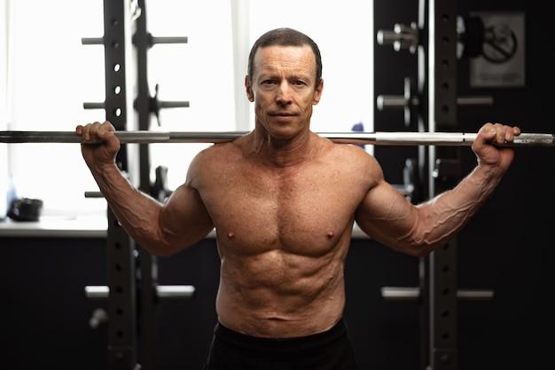Älterer mann, der im fitnessstudio kniebeugen macht