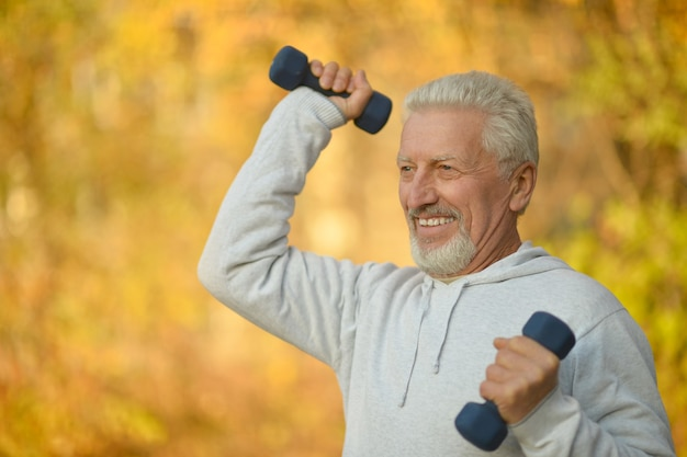 Älterer mann, der im herbstpark mit hanteln trainiert