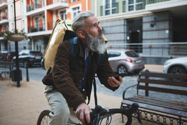 Älterer mann, der im lieferservice unter verwendung des fahrradfahrens des smartphones arbeitet