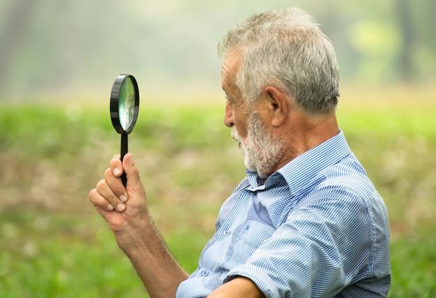 Älterer mann, der im park sich entspannt.