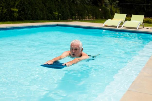 Älterer mann, der im pool an einem sonnigen tag schwimmt