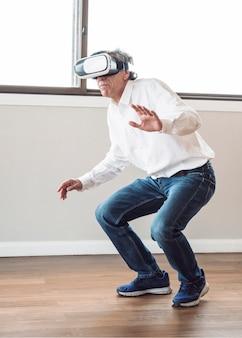 Älterer mann, der im raum erfährt virtuelle realität steht