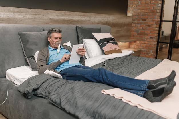 Älterer mann, der im schlafzimmer zu hause durch sauerstoffmaske inhaliert und seinen laptop benutzt.