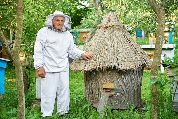 Älterer mann, der imkerkostüm trägt, das honig an seinem bienenhaus im freien kopyspace erntet.