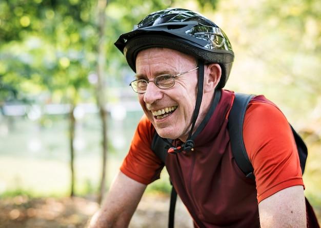 Älterer mann, der in den park radfährt