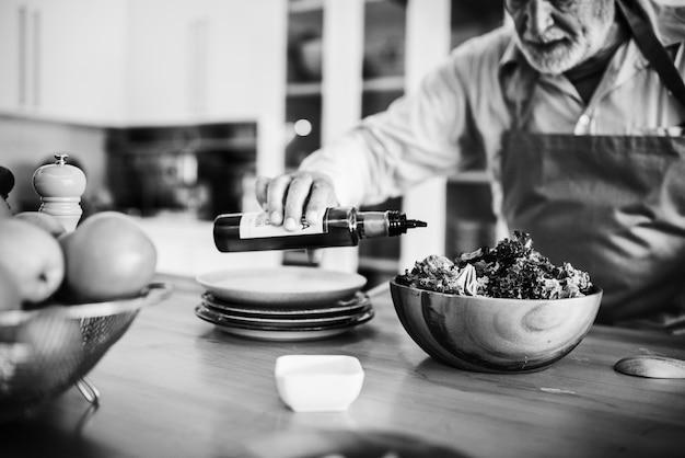 Älterer mann, der in der küche kocht