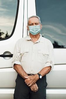 Älterer mann, der in der neuen normalität am wohnmobil steht