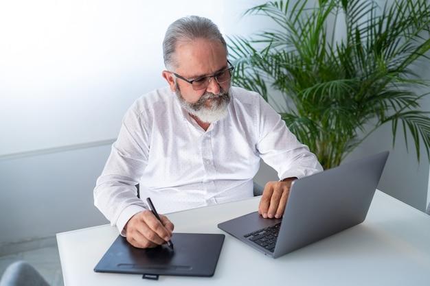 Älterer mann, der in seinem büro mit laptop und tablet arbeitet