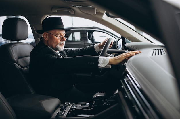 Älterer mann, der innerhalb eines autos sitzt