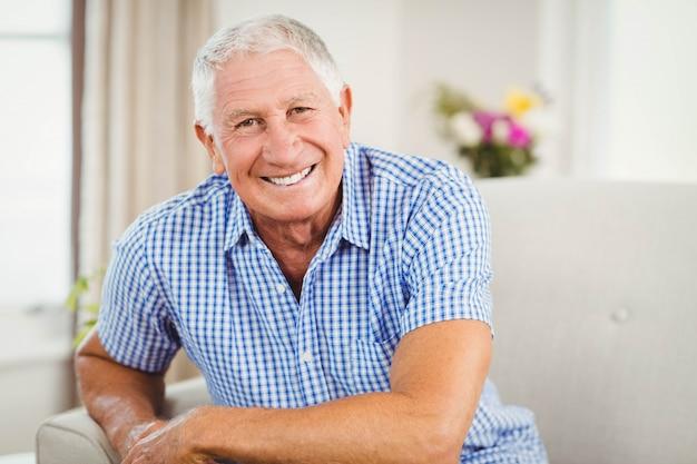 Älterer mann, der kamera betrachtet und im wohnzimmer lächelt